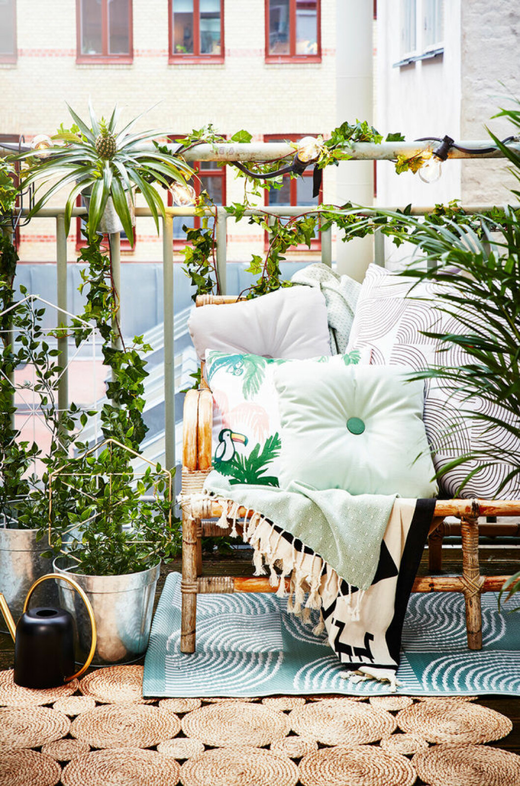 Summer balcony with plants and pillows.
