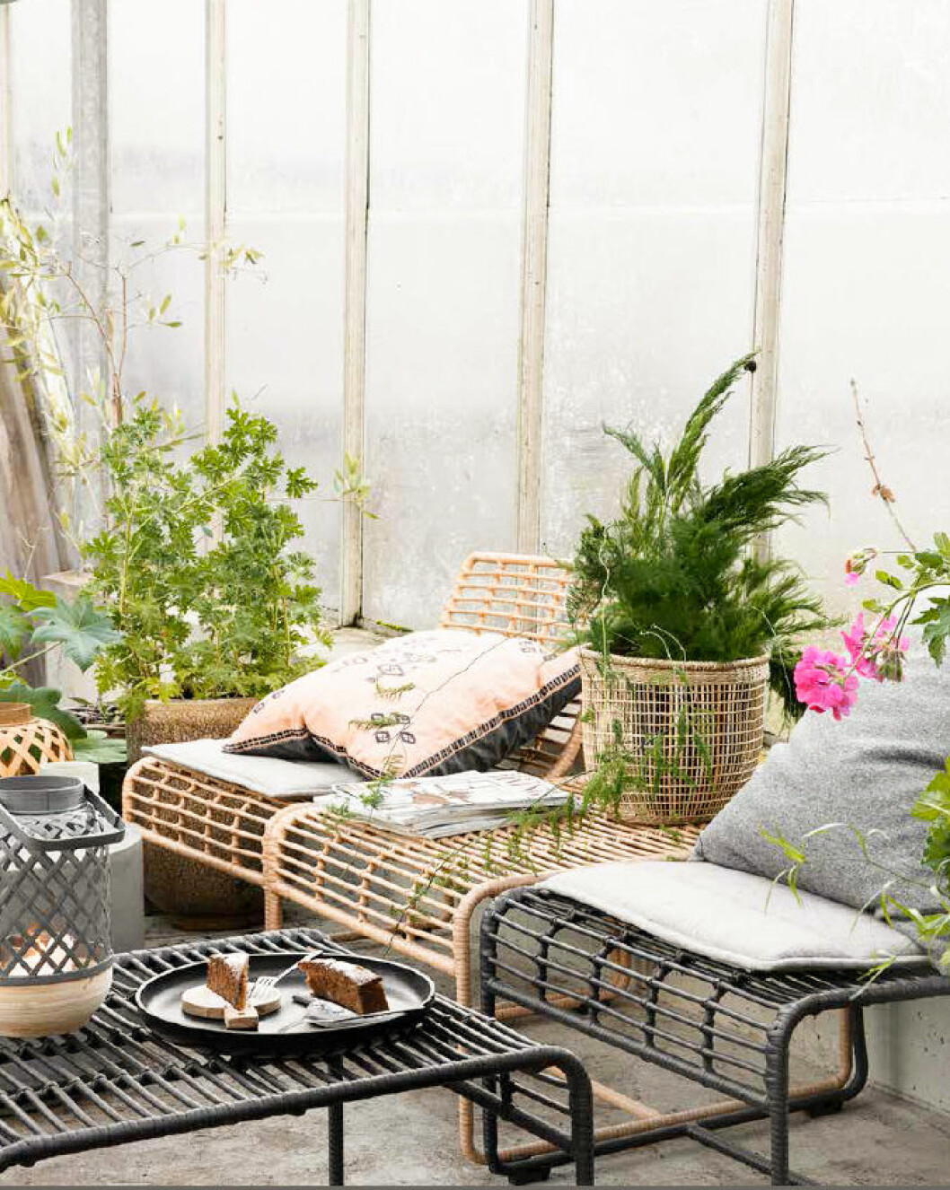 Rattan chairs at the balcony with pillows and plants. Outdoor furniture from House doctor.