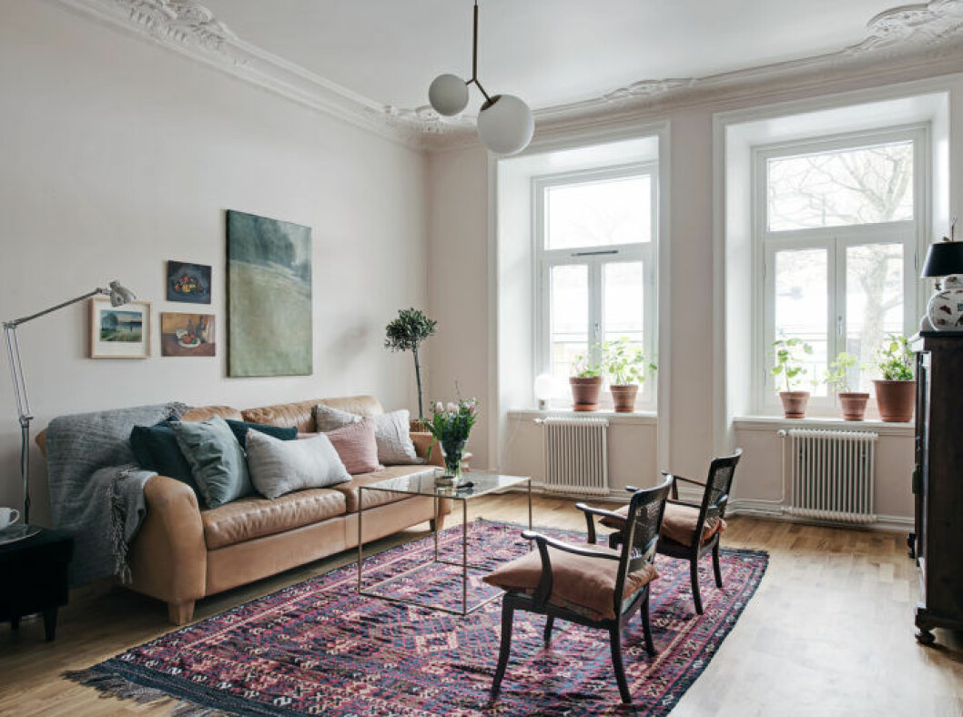 Bohemian styled livingroom with leather sofa, persian styled rug and vintage chairs.