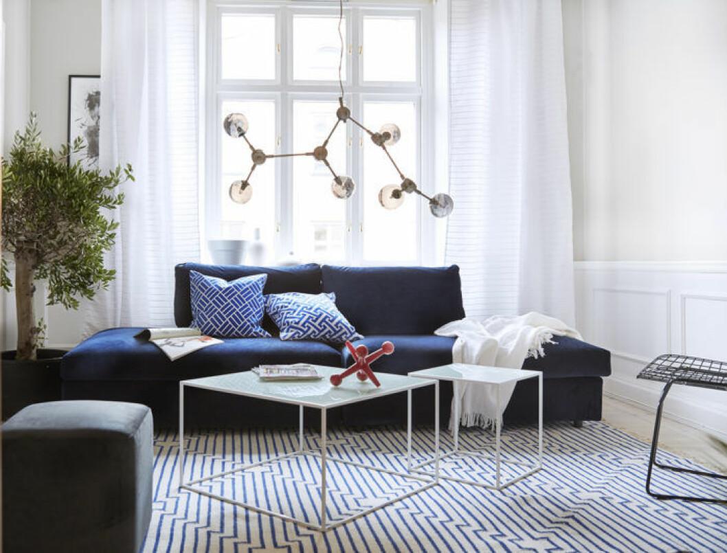 Vardagsrum med blå soffa och trendig taklampa. Jotex vårnyheter 2018.