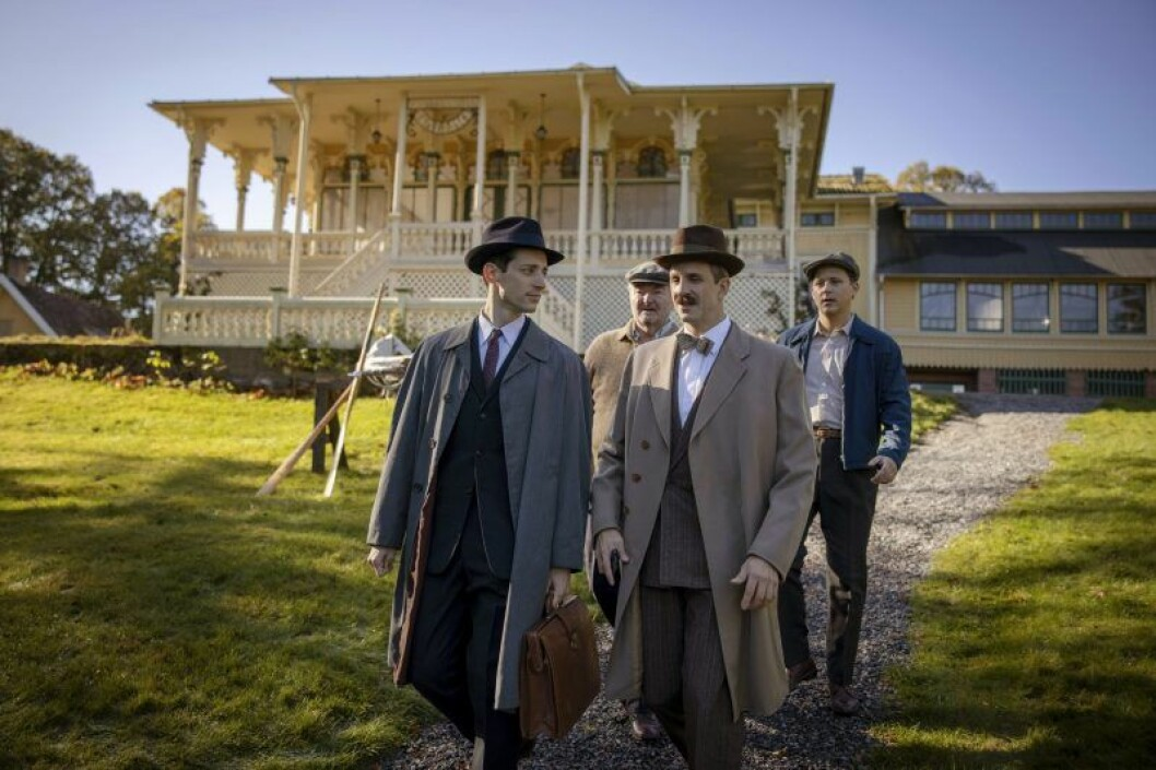 fyra herrar i kostym framför ett stort hus