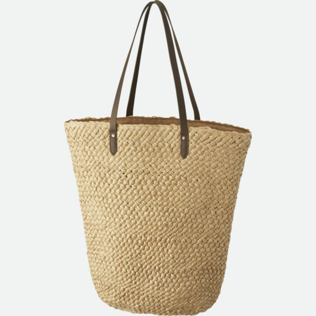 Strandväska i flätad bast och bruna remmar.