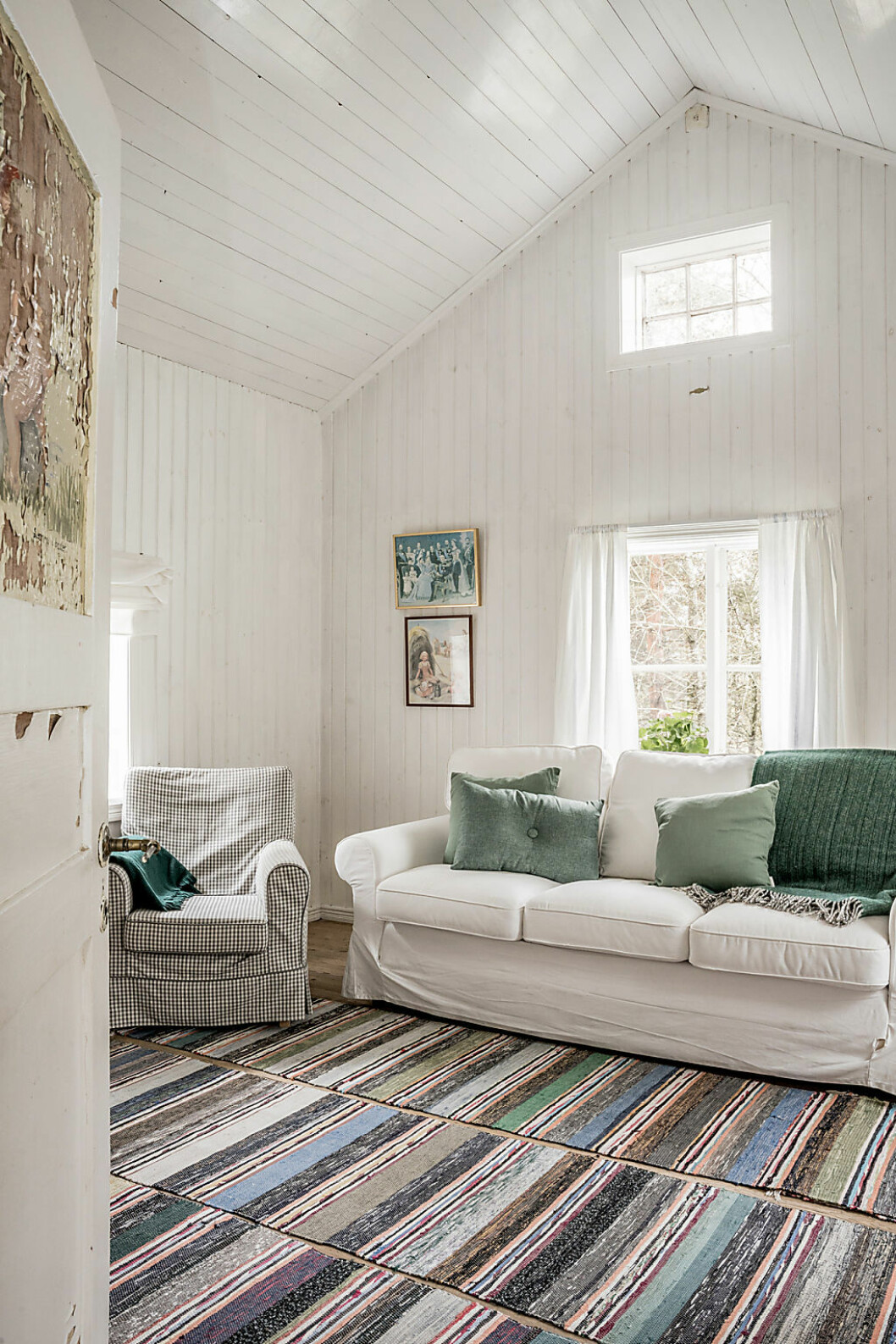 Det lilla vardagsrummet bjuder trots sin storlek på en imponerande takhöjd – ett måste för att få plats med ett rymligt sovloft.