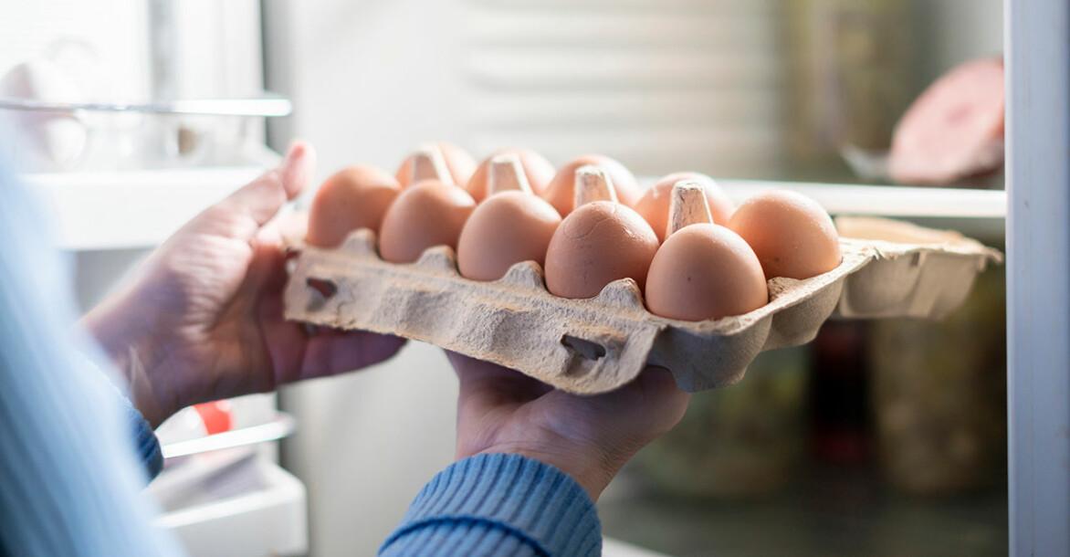 Kvinna ställer in ägg i kartong i kylskåpet