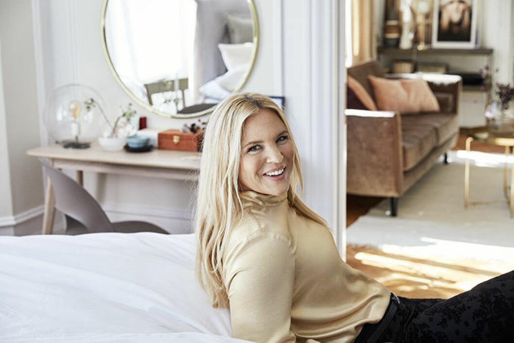 Anja Pärsson i guldig silkig topp med halvpolo-krage och svarta byxor, ur kollektionen för Ellos.