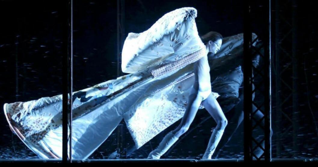 En modell står i en vindtunnel med en lång cape fladdrande bakom sig.