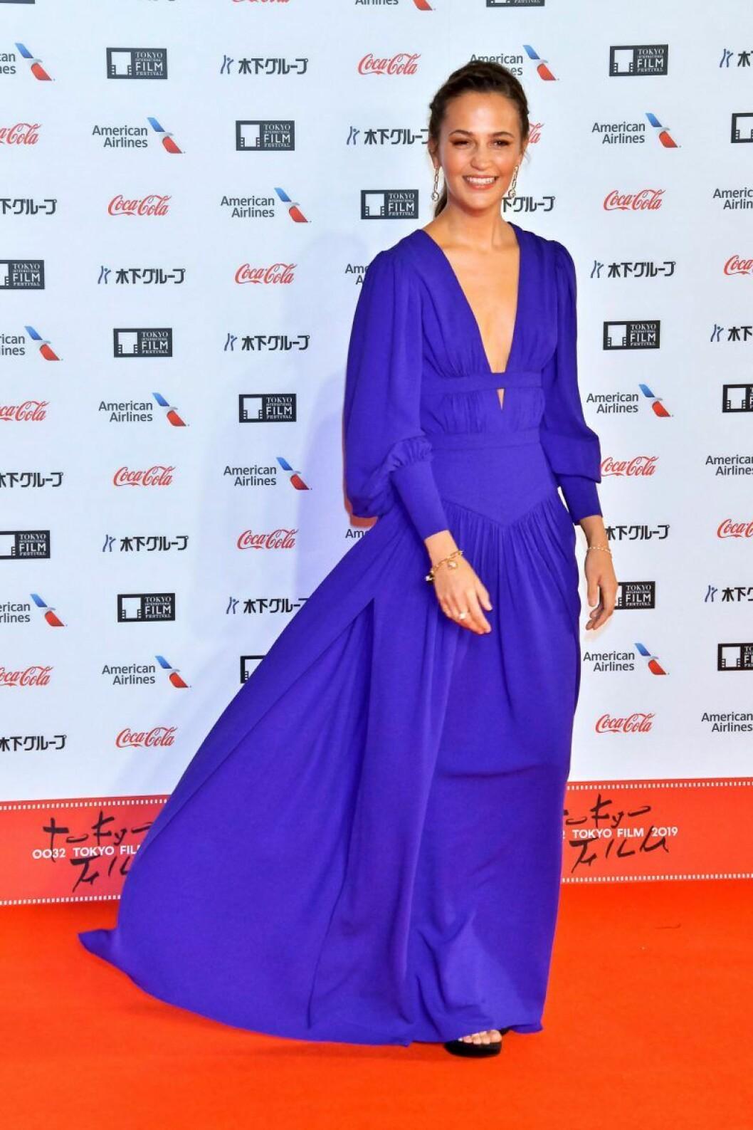 Alicia Vikander på röda mattan i en blåturkos klänning