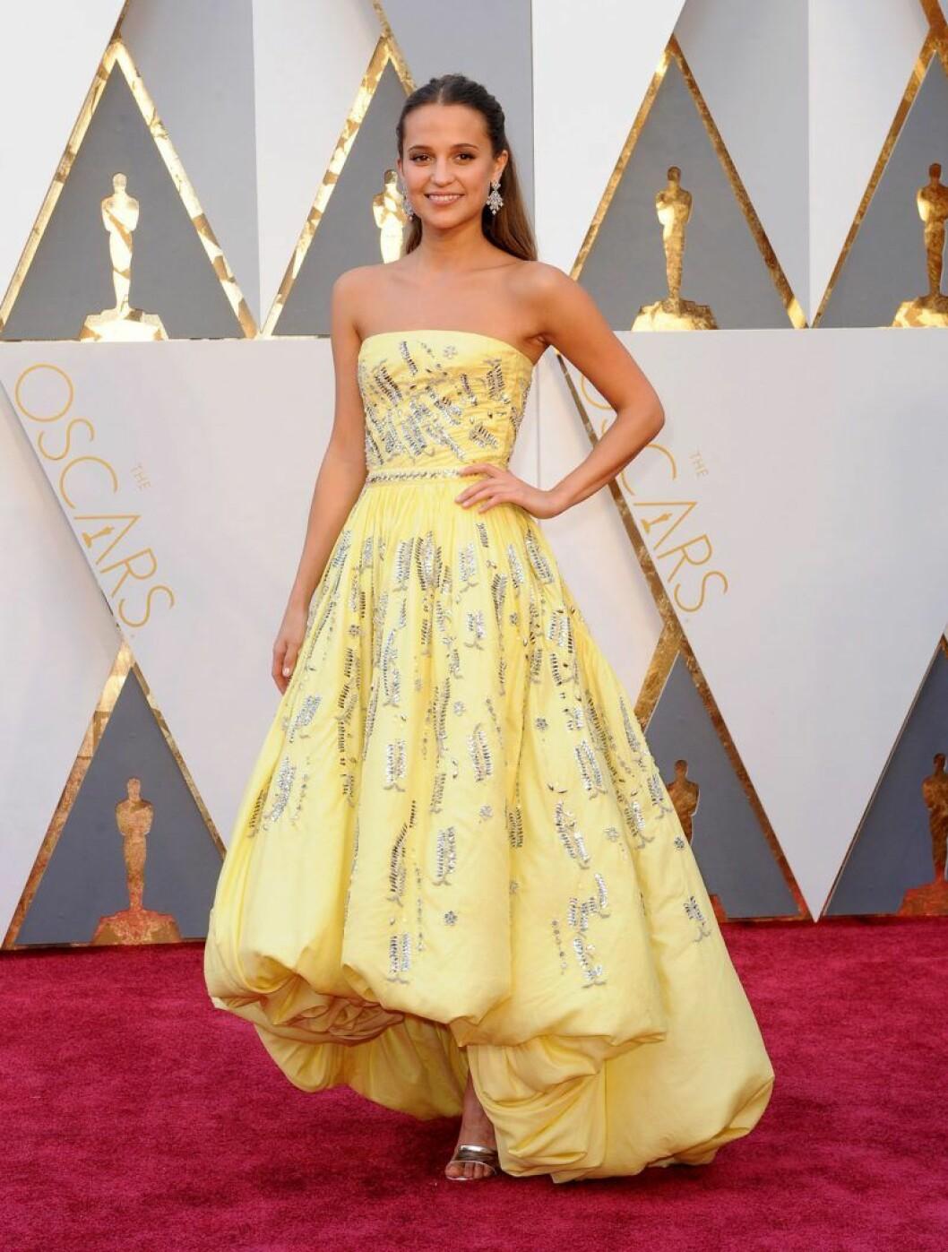 Alicia Vikander i en gul klänning