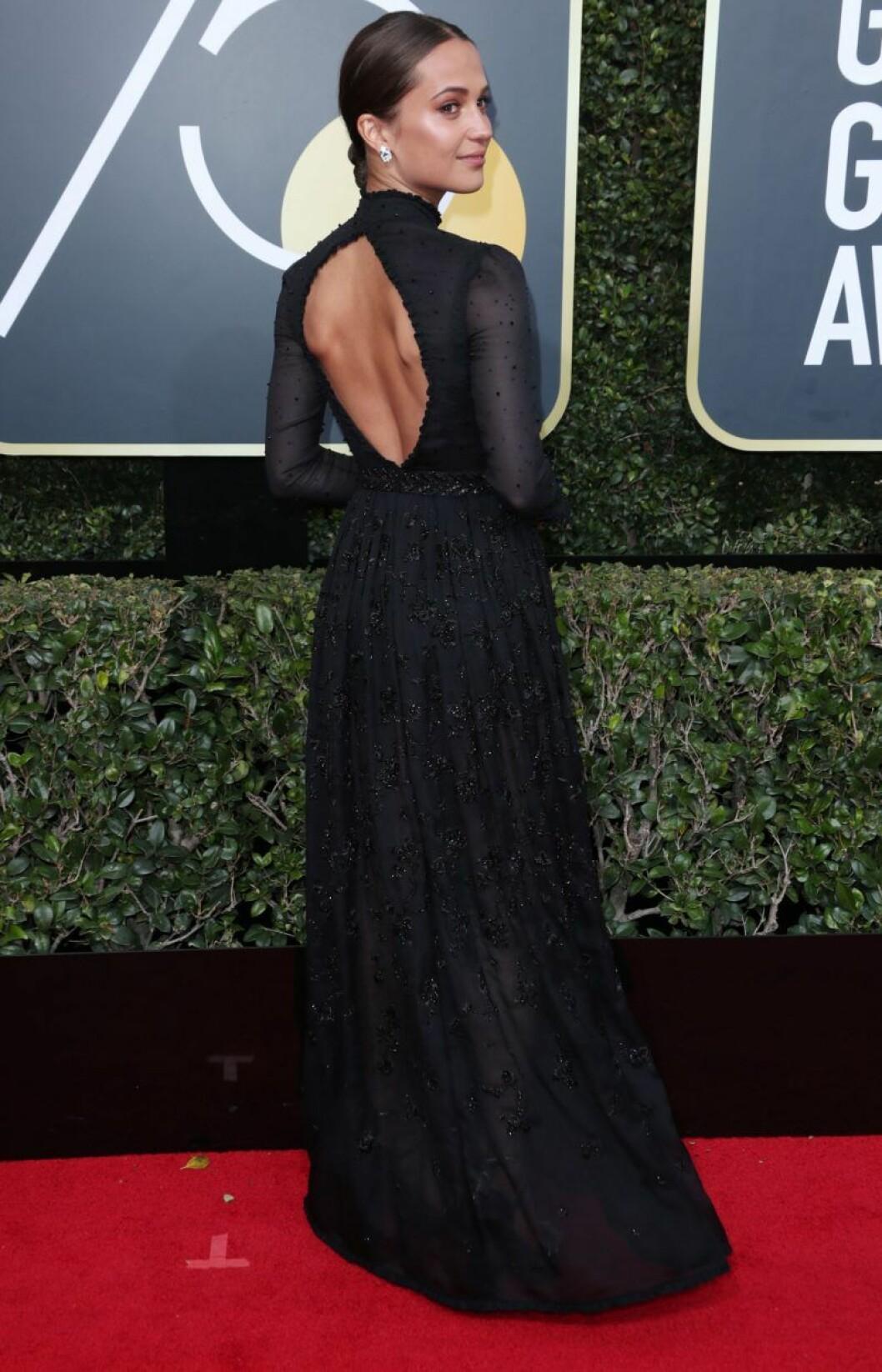 Alicia Vikander i svart klänning med öppen rygg