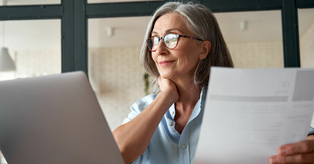 en kvinna med grått hår och glasögon tittar i papper och på sin dator