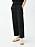 Svarta, dressade byxor i trekvartsmodell i linne. Plåtade på modell ihop med vita sneakers. Byxor från Arket.
