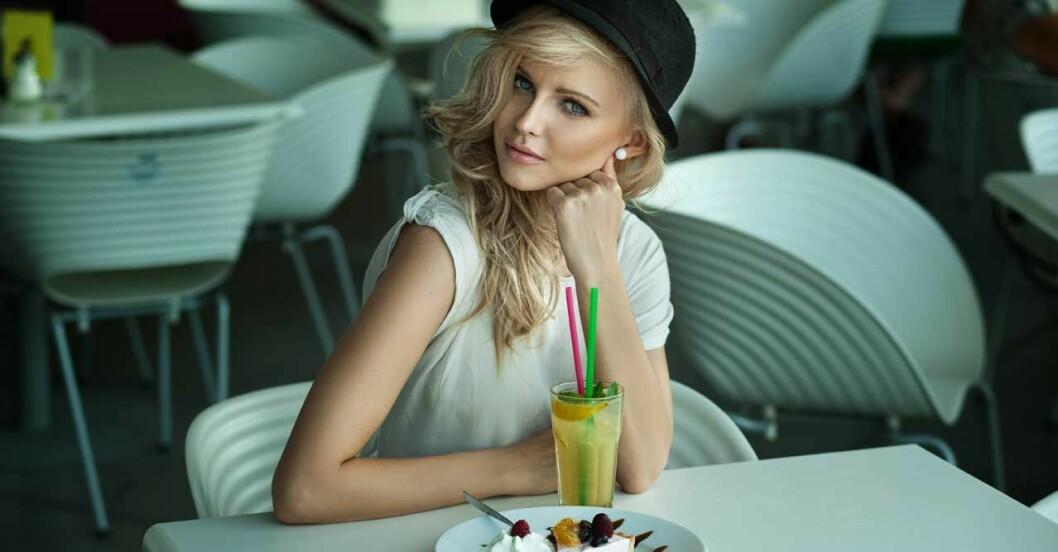 kvinna med hatt och armbågarna på bordet