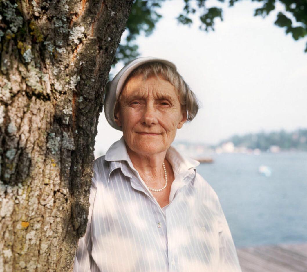 Astrid Lindgren tittar fram bakom ett träd 1987.