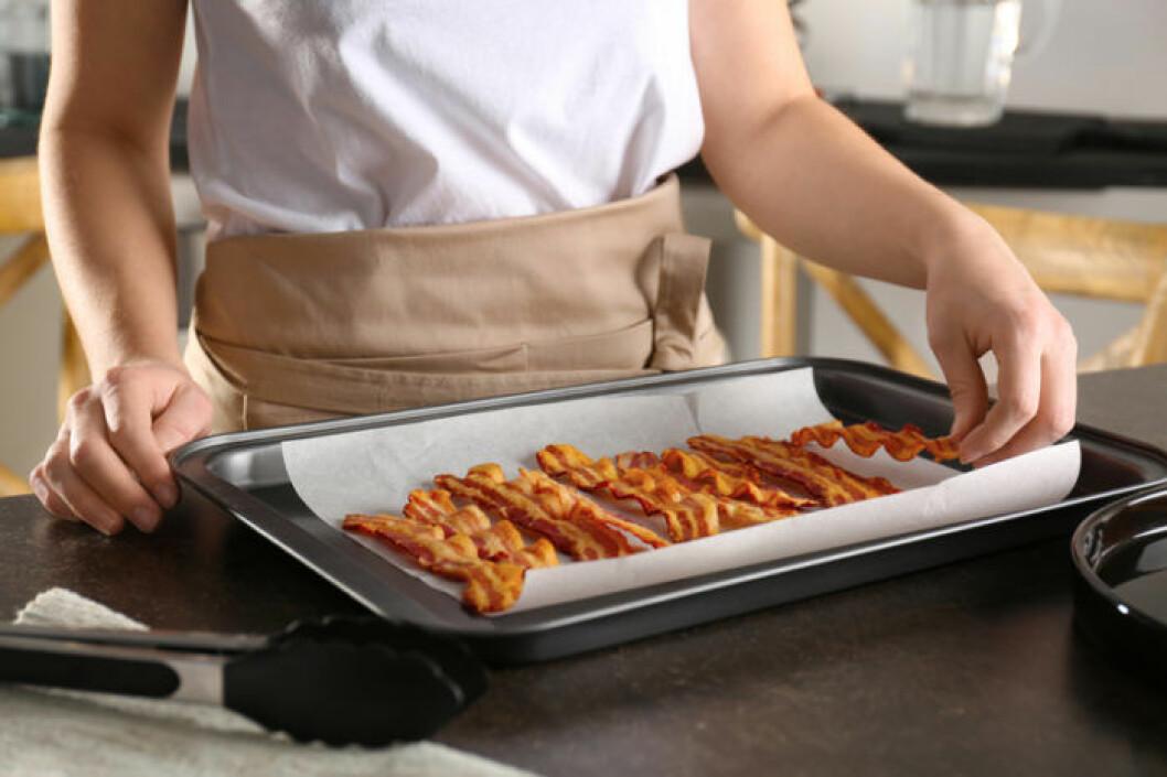 Kvinna med plåt med bacon tillagad i ugn.