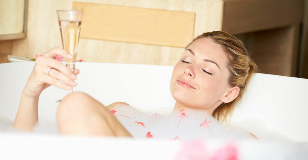tjej som ligger i badkar och dricker champagne
