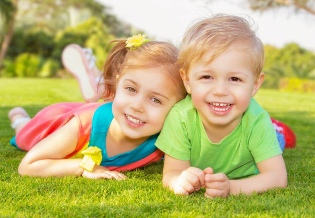 Två barn ligger i gräset.