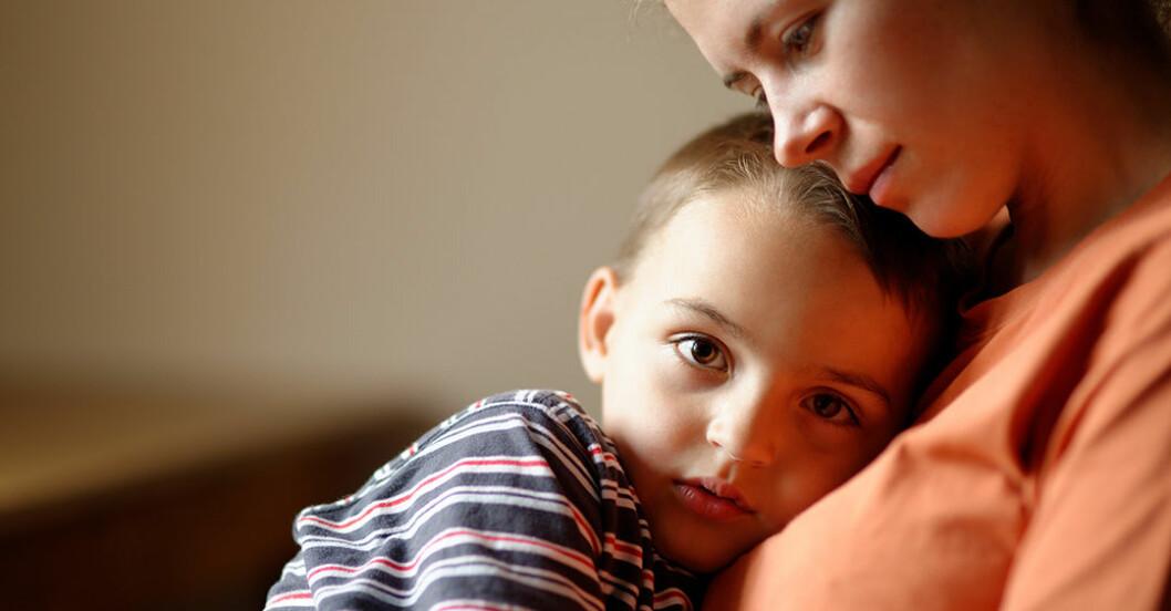 Liten pojke med oro i blick kramar sin mamma