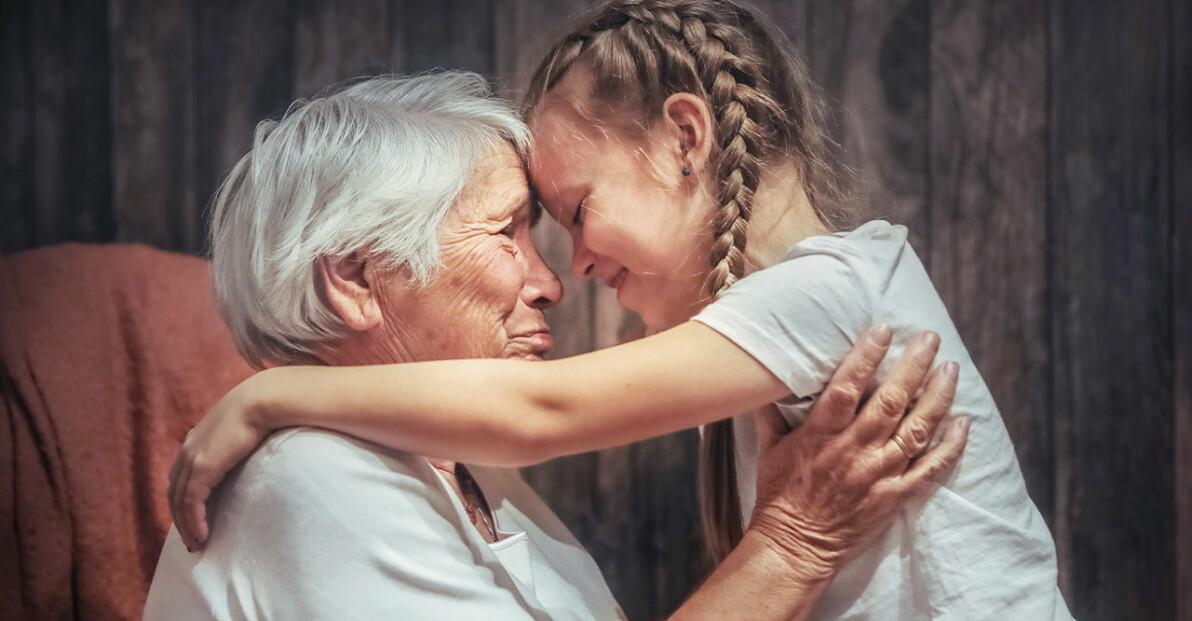 gammal kvinna med vitt hår kramar sitt barnbarn som har flätor i håret