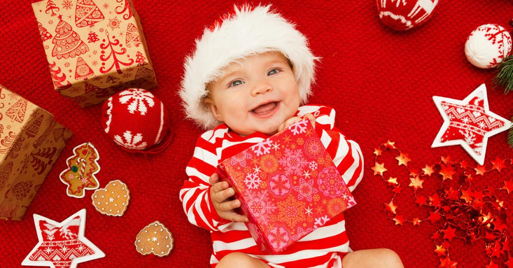 en bebis i tomteluva som håller i ett paket och skrattar