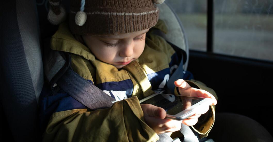 Bebis sitter med telefon i bilen