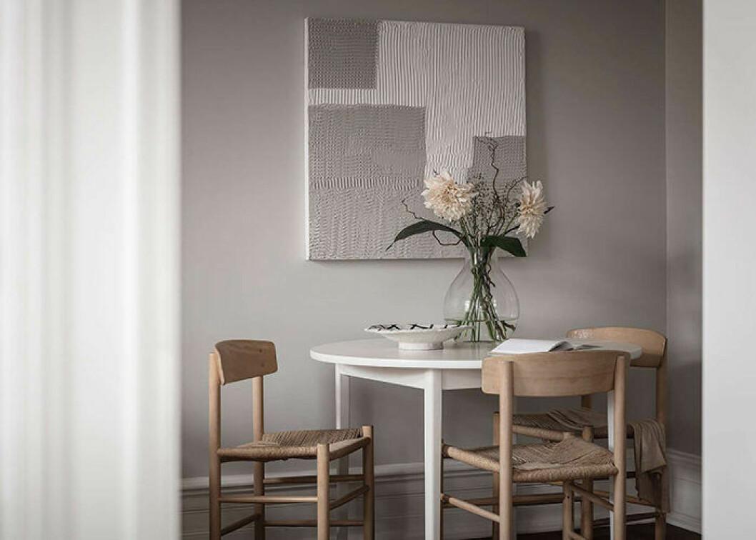 Beige väggar och stolar i naturlig träfärg med tavla i beige och vitt