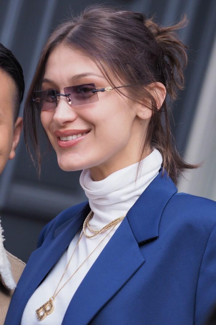 bella hadid ler och har 90-talsglasögon på sig