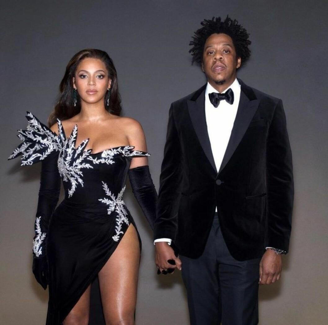 Beyoncé och Jay Z håller varandra i handen och tittar rakt fram