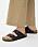 Tofflor med skinnremmar i svart med två remmar. Platt sula och spännen. Sandaler från Birkenstock.
