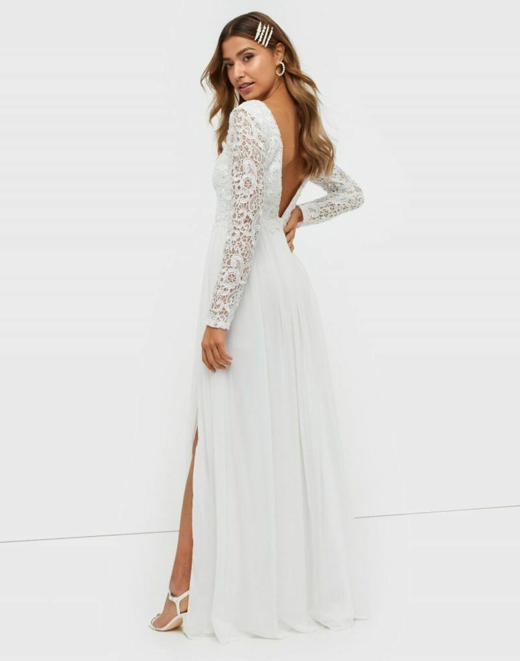 En bild på en långärmad brudklänning med v-ringad rygg och hög slits från Nelly.