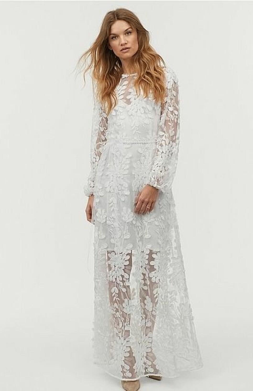 En bild på en långärmad brudklänning i mesh med blom- och paljettdetaljer från Ellos.