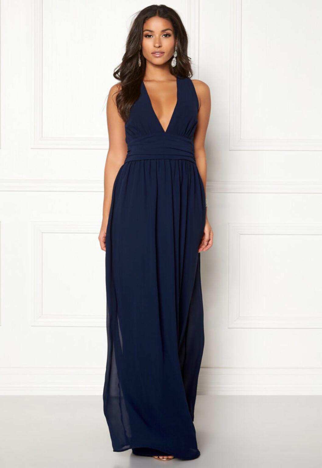 En bild på en mörkblå långklänning i klassiskt snitt från Bubbelroom.