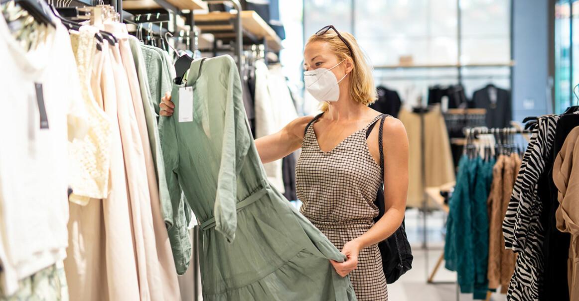 Kvinna med munskydd tittar på kläder i butik