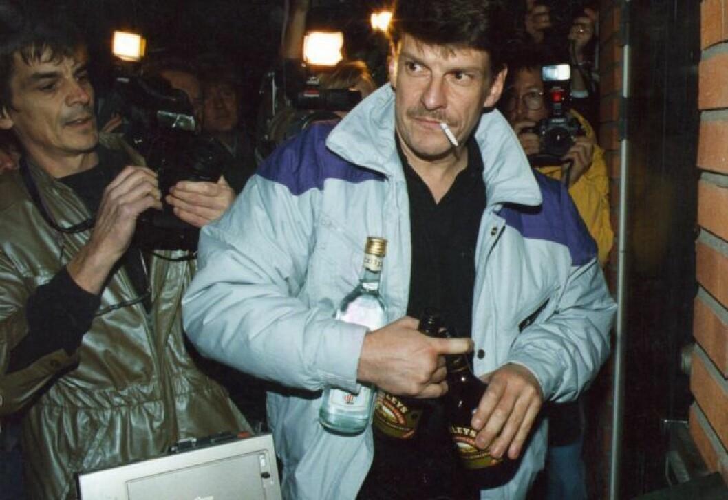 En man har ljusblå jacka på sig och en cigarett i mungipan. I handen har han flera flaskor med alkohol