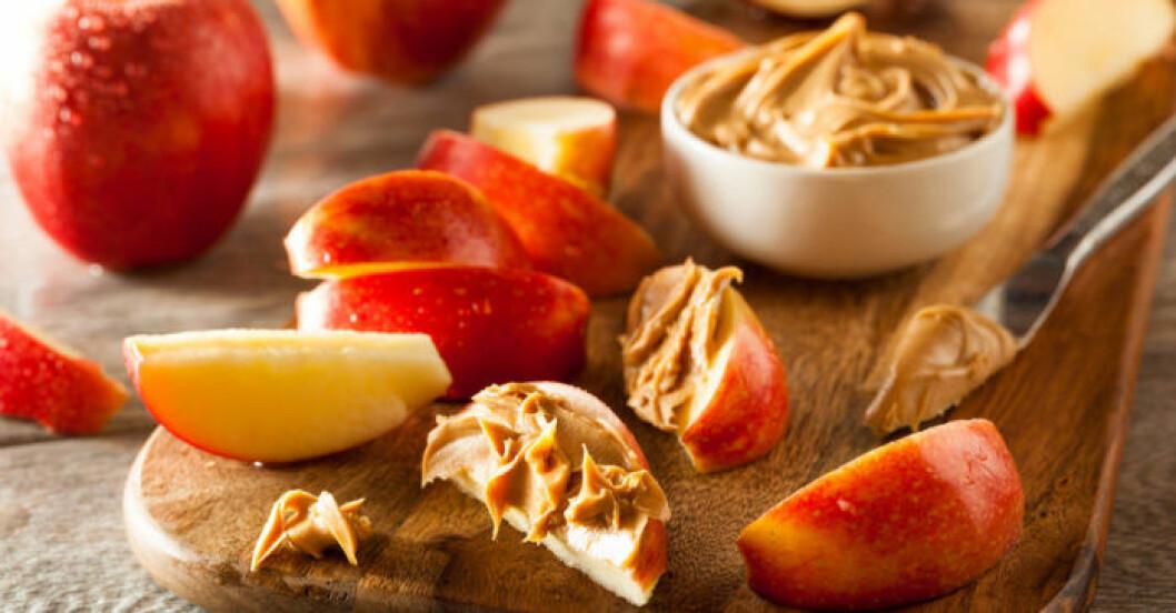 Äppelklyftor doppade i krämigt jordnötssmör botar effektivt sötsuget.