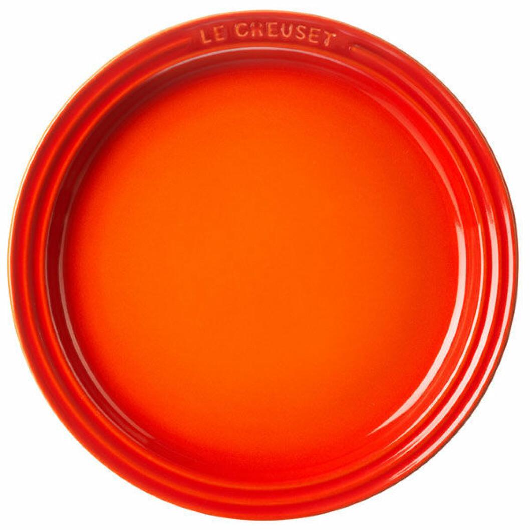 Le Creusets tallrik i eldigt orange.