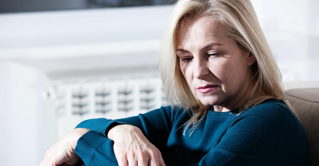 Kvinna som lider av depression sitter på sin säng