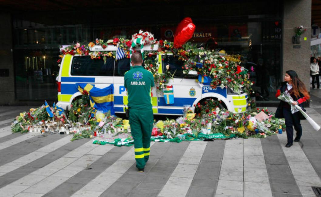 Drottninggatan i Stockholm april 2017. En målad polisbil täckt med blommor. Framför står en ambulanssjukvårdare och tittar på polisbilen.