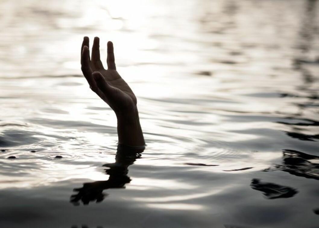 Hand som sticker upp ur vatten.