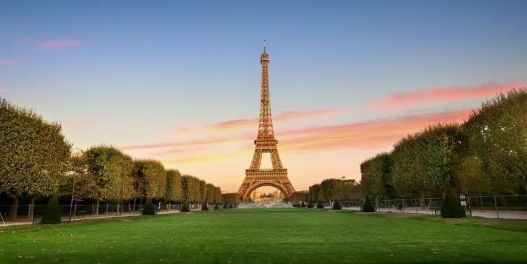 Eiffeltornet i paris med en grön gräsmatta framför
