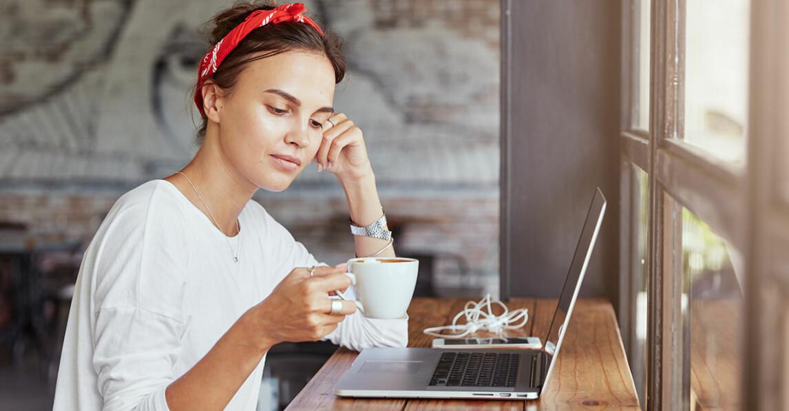 Kvinna sitter vid sin dator med en kaffekopp