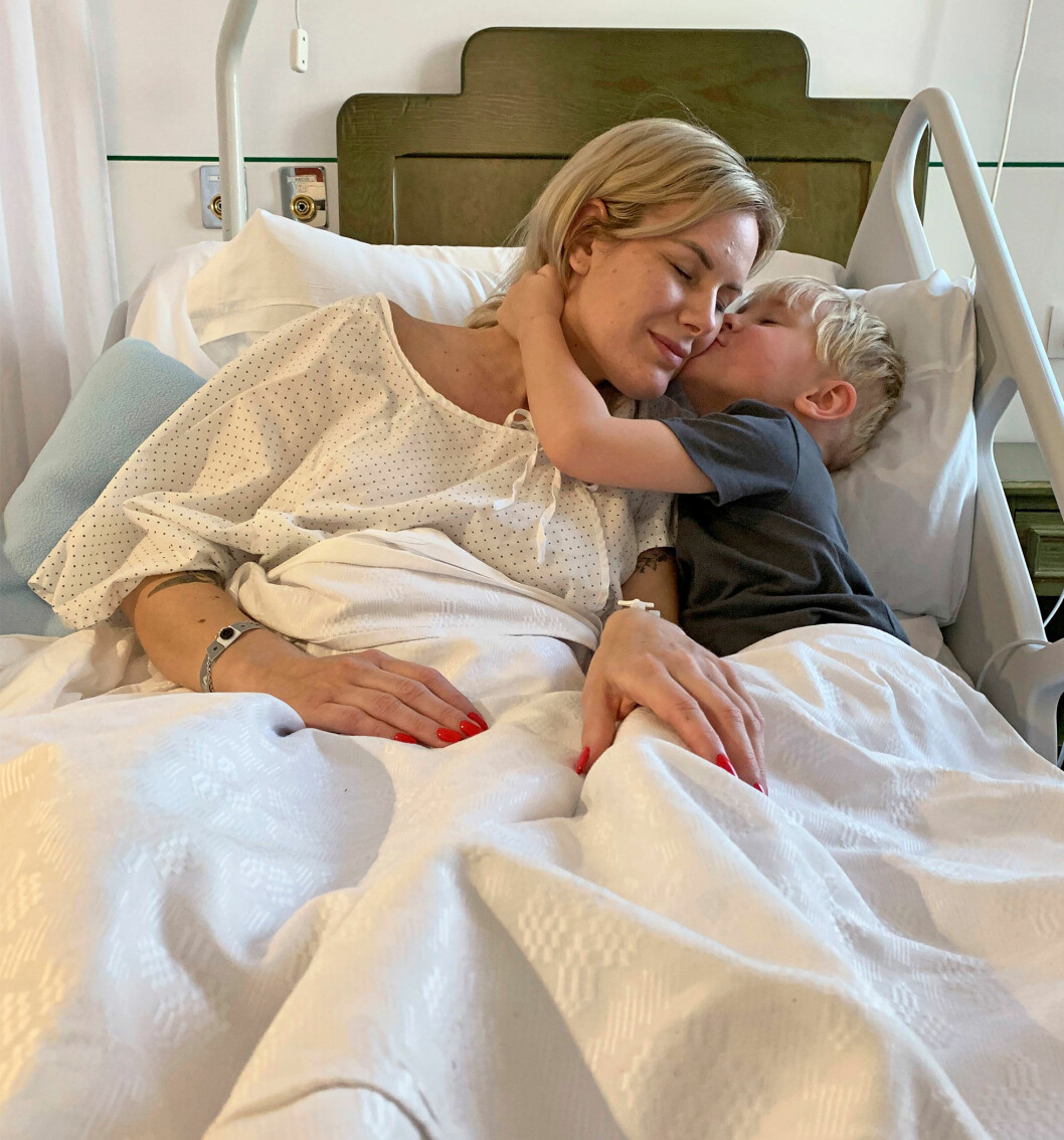 Elin ligger i en sjukhussäng och får en puss av sin lille son.