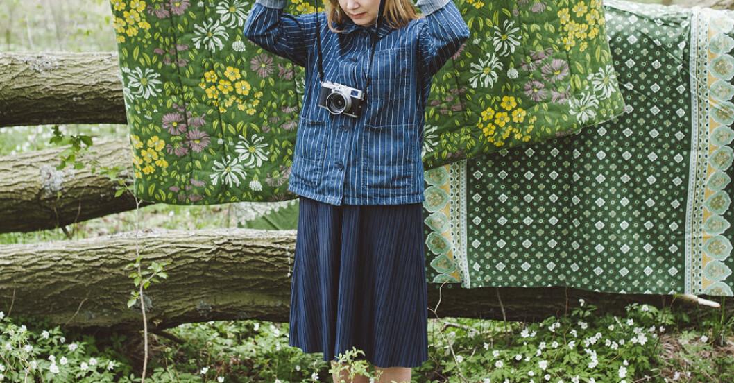 Kvinna i skogen med kamera