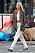 Modellen Elsa Hosk i brun, oversizad blazer, vit, magkort topp, brunt skärp, vita jeans, beige clutch och mönstrade träskor av märket Dior, på fötterna.