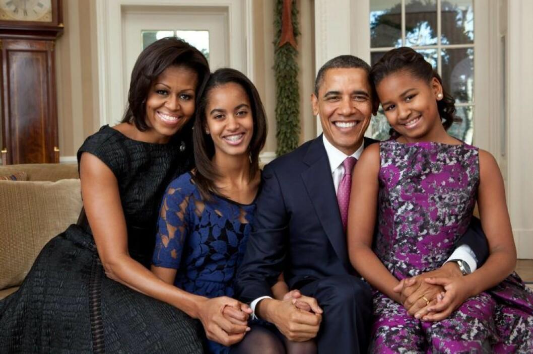Michelle, Malia, Barack och Sasha Obama. sitter i en soffa finklädda och ler.