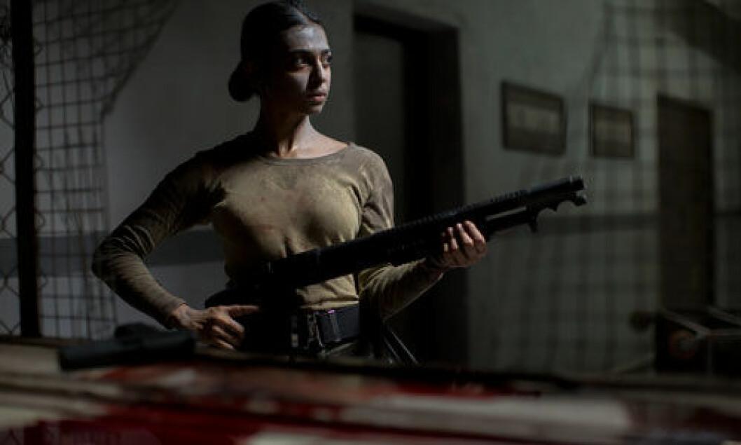 Radhika Apte spelar förhörsledaren Nida i tv-serien Ghoul. Här håller hon i ett vapen.