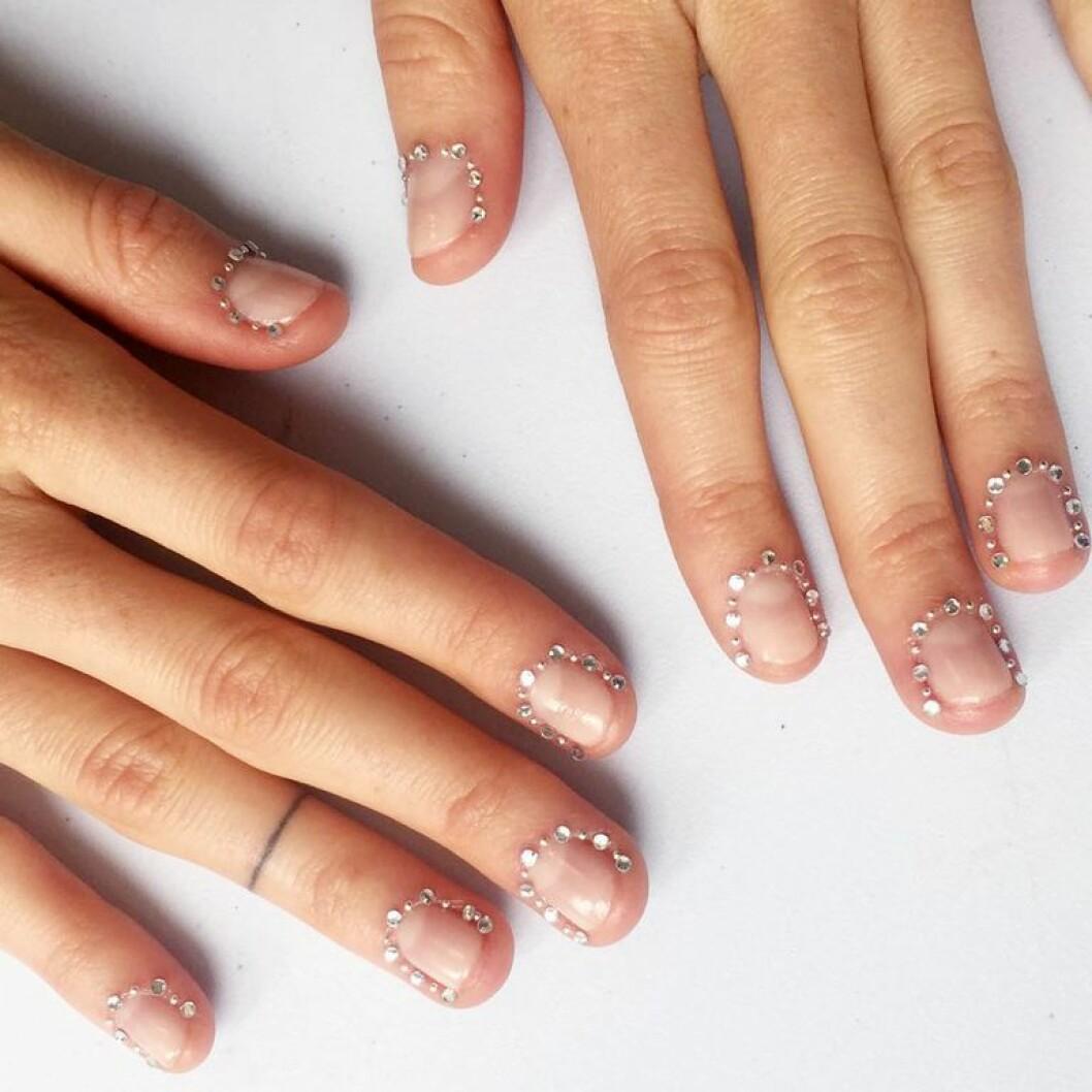 En bild på en skimrande manikyr med glittrande stenar runt nageln.