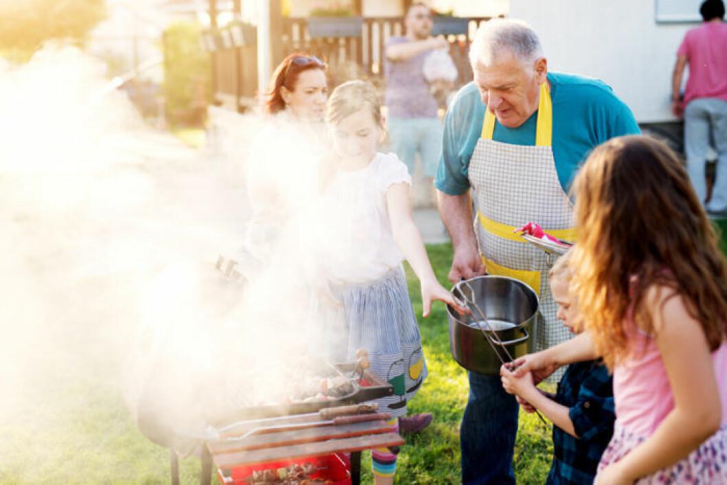 Äldre man grillar med sina barnbarn. Det röker väldigt mycket från grillen.
