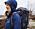 Bild på kvinna i blå jacka med luva och stor, svart ryggsäck på ryggen. Outfit från Haglöfs.