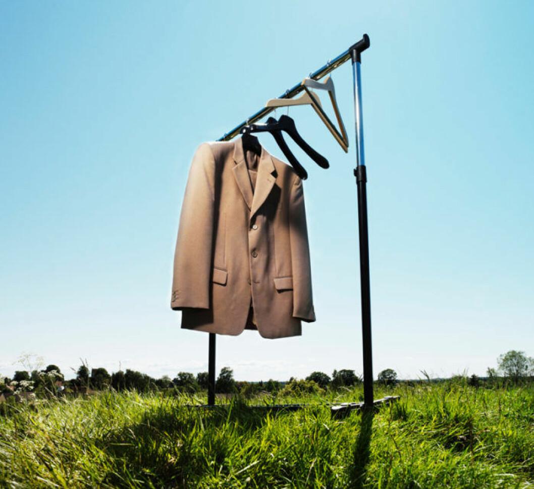 Kavaj hänger på klädställ på fält.