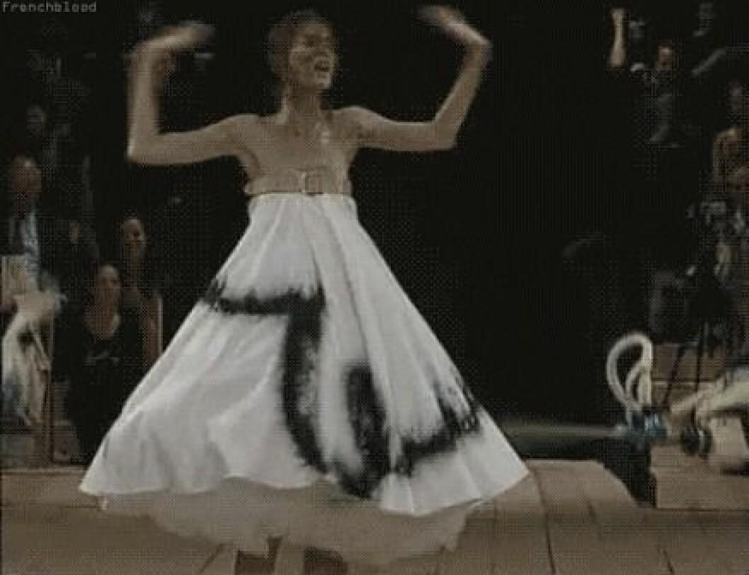 En modell blir nersprutad av robotar på catwalken. Visningen av McQueen ägde rum 1999.